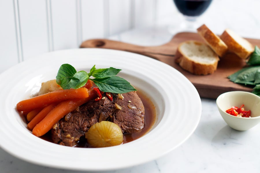 vietnamese beef stew in white bowl with platter of sliced bread in background