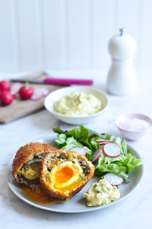 scotch eggs with salad on plate