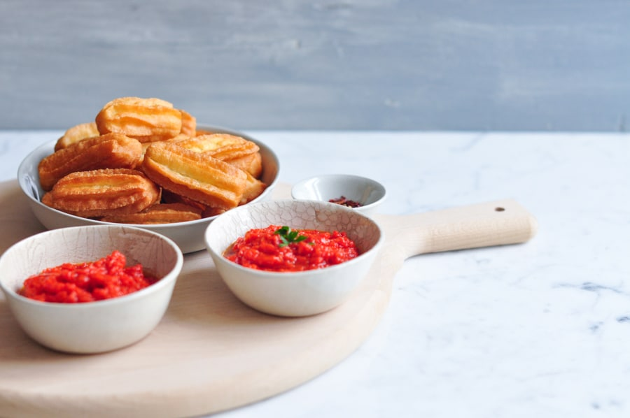 potato churros with bowls of red pepper sauce