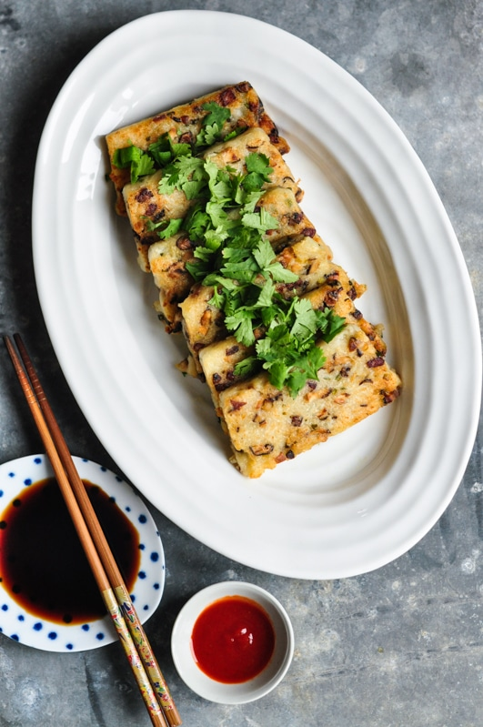 chinese turnip cake sliced on white plate with small bowls of sauce