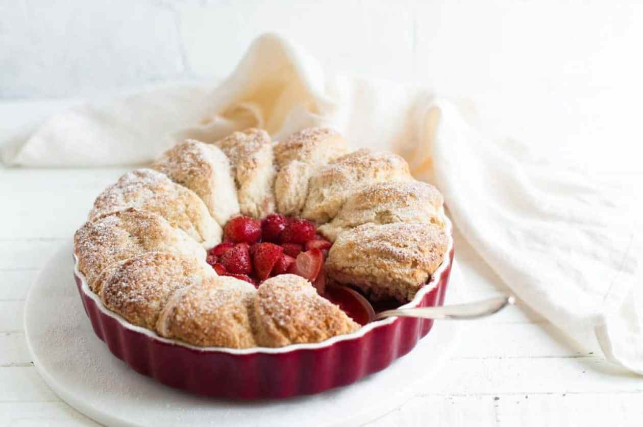 strawberry cobbler in red pie dish