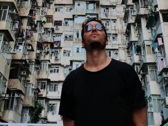 rayan à hong kong devant des immeubles