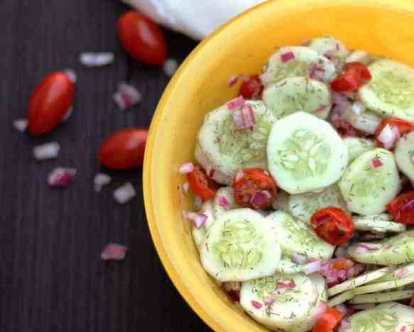 cucumber tomato salad in yellow bowl