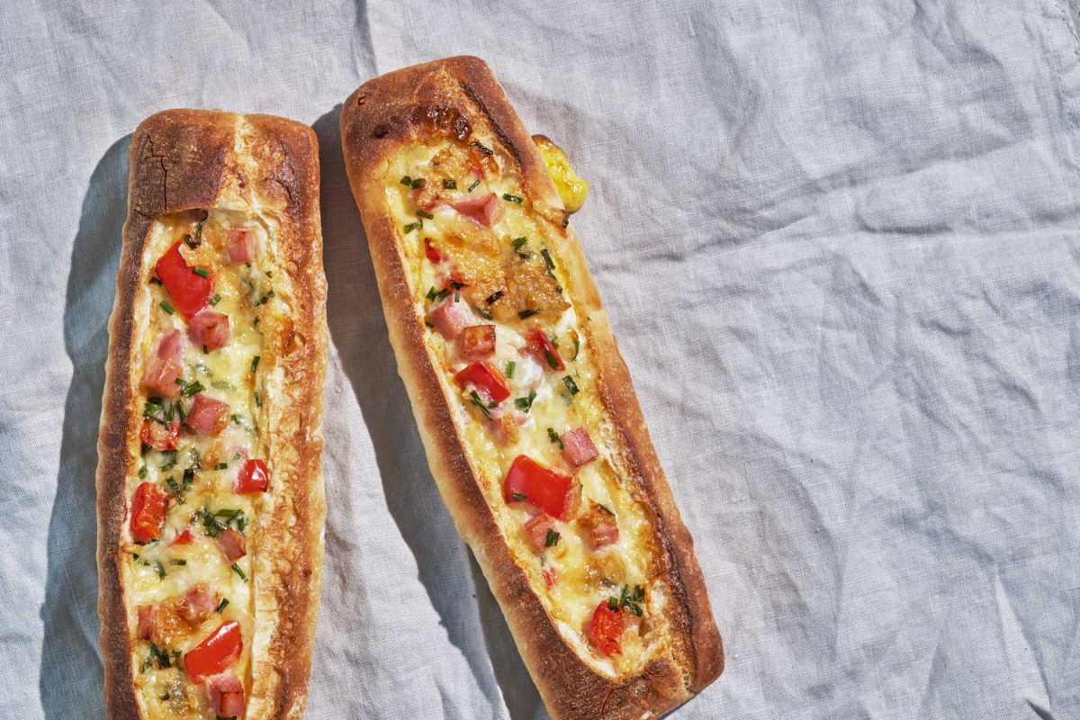 Two Crispy Creamy Egg Boats on parchment paper - loaves of crunchy bread with eggs, tomatoes, green onions and cheese baked inside.