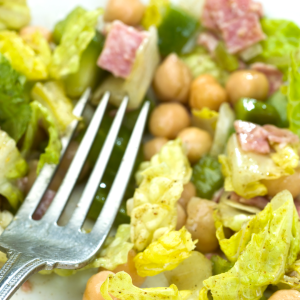 Closeup of a chopped italian salad with salami and chickpeas