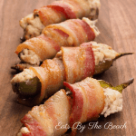bacon wrapped cheese filled jalapeno peppers on wooden board