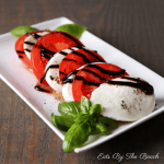 White plate with sliced tomato, mozzarella cheese with a drizzle of balsamic glaze and a garnish of fresh basil leaves.