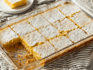 Glass pan of lemon bars with a shortbread crust and dusted with powdered sugar