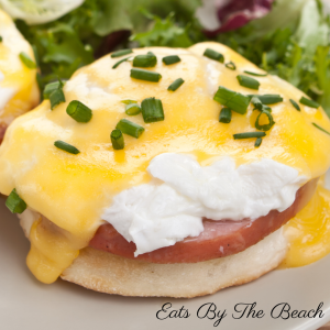 Dish of classic eggs benedict-buttery english muffin, salty, crispy Canadian bacon, poached egg & silky hollandaise sauce. Garnished with chopped chives. Delicious recipe from Eatsbythebeach.com
