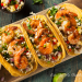 Spicy shrimp tacos with sweet and crunchy slaw on a serving platter