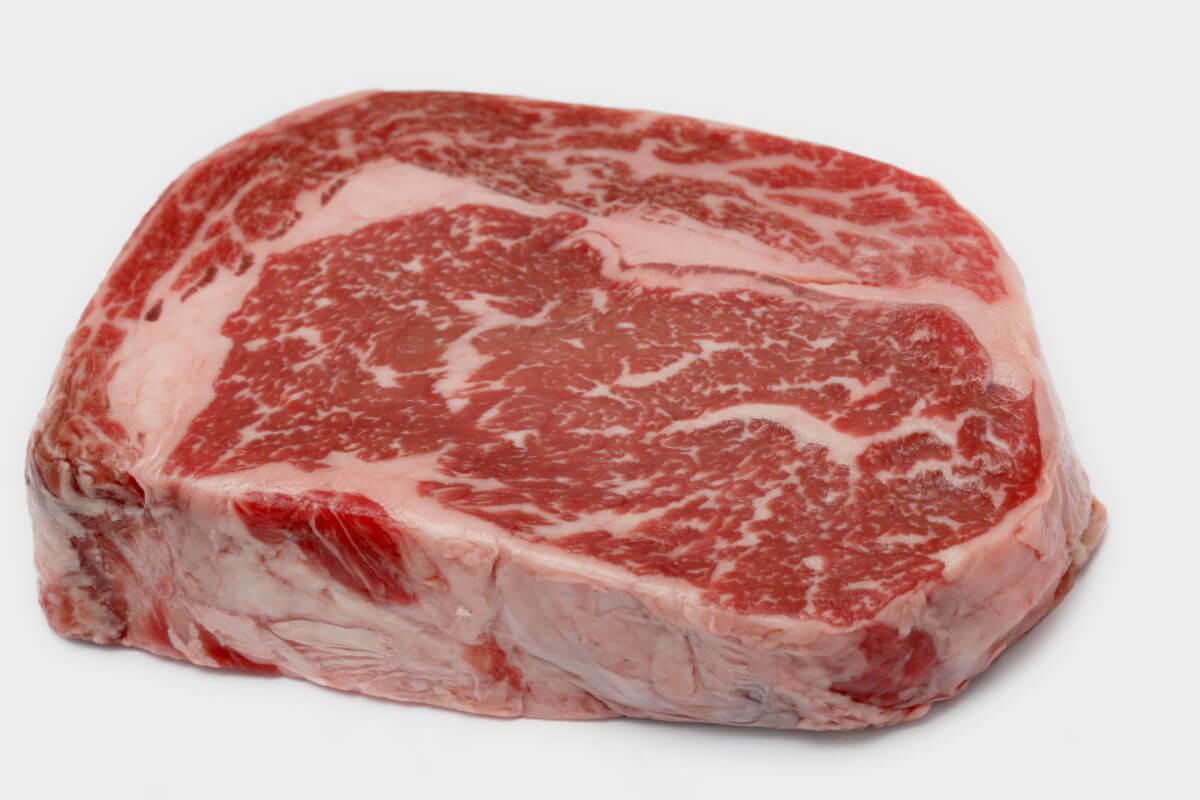 A raw, well marbled ribeye steak.