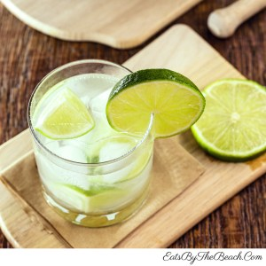 A Brazilian cocktail of Cachaca, lime, and sugar served in a highball glass garnished with a slice of lime.