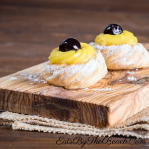 A classic Italian pastry, this wooden board with two zeppole pastries filled with almond scented Italian pastry cream and garnished with a syrupy amarena cherry.