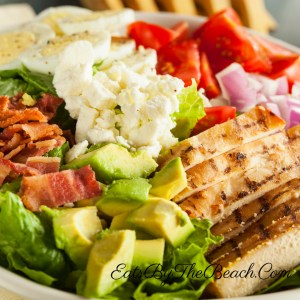 A cobb salad with grilled chicken, egg, bacon, avocado, tomato, onion, and feta cheese with a homemade Catalina-Style French dressing.