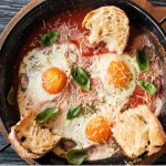 Cast iron skillet with spicy Italian tomato sauce and poached eggs, garnished with parmesan cheese and basil. Served with a side of Italian bread.