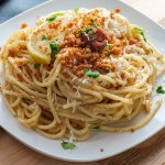Plate of spaghetti with an olive oil, garlic, breadcrumb, lemon zest, and Parmesan cheese sauce. This is classic Italian fare.