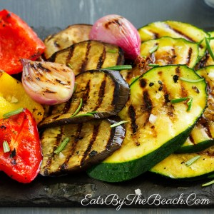 A slate platter of grilled zucchini, eggplant, onions, and red bell pepper with a garlic, rosemary, and balsamic glaze.