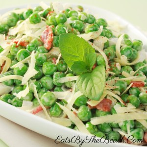 Bowl of a pea salad with onion, cheese, and a tangy dressing.