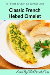 A white plate with a perfectly rolled, soft, and custardy Classic French Herbed Omelet.
