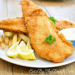 Crunchy batter fried fish served with potato chips and lemons