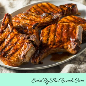 A platter of grilled bbq pork chops - bone-in pork chops with a homemade dry rub and basting sauce are so flavorful, juicy, and tender.