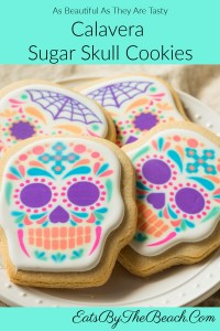 A plate of Calavera Sugar Skull Cookies - skull shaped cookies with a fondant icing and decorated to resemble the colorful Mexican Day Of The Dead skulls. As pretty as they are tasty.