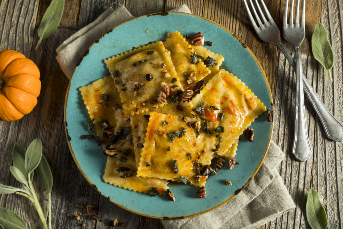 Turquoise plate with Pumpkin Ravioli-In-Sage-Brown-Butter-Sauce, garnished with sage and hot sauce.