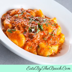 Bowl of homemade Ricotta Gnocchi In Easy Pomodoro Sauce and garnished with a sprinkle of fresh herbs.