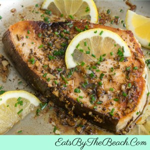 A skillet with Lemon Garlic Roasted Swordfish, garnished with lemon slices and chopped chives in a lemon, wine sauce.