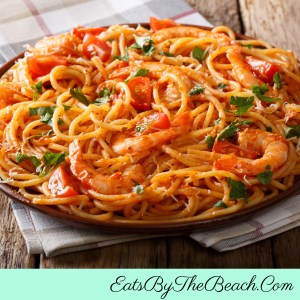 Bowl of Shrimp Fra Diavolo - juicy shrimp sauteed in a spicy, fresh tomato sauce served over pasta and garnished with parsley and Parmesan cheese.