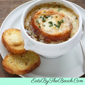 White crock of French Onion Soup with melted gruyere cheese and a crusty, garlicky crouton. Delicious comfort food.
