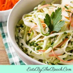 A bowl of cool, crunchy vinegar based coleslaw - made with cabbage, carrots, onion, and cilantro in a sweet and sour vinegar sauce. Perfect to go with barbecued meats.