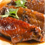Close-up view of a plate of Green Tea Glazed Chicken Wings - baked chicken wings that are glazed in a spicy, tangy, green tea sauce