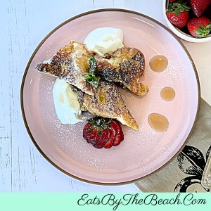Plate of Chef Rachel's French Toast with chantilly cream, strawberries, and dusting of powdered sugar.