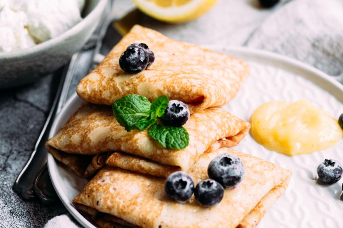 Closeup of lemon blueberry Bavarian pancakes garnished with fresh blueberries and fresh mnt.