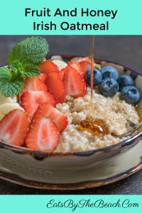 Bowl of warm and heart fruit and honey Irish oatmeal with sliced bananas, sliced strawberries, blueberries, and a drizzle of honey.