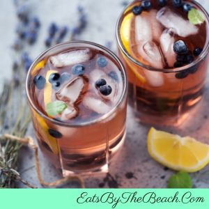 Highball glasses with Lemon Blueberry Lavender cocktails garnished with lemon twists, blueberries, and a sprig of fresh lavender.