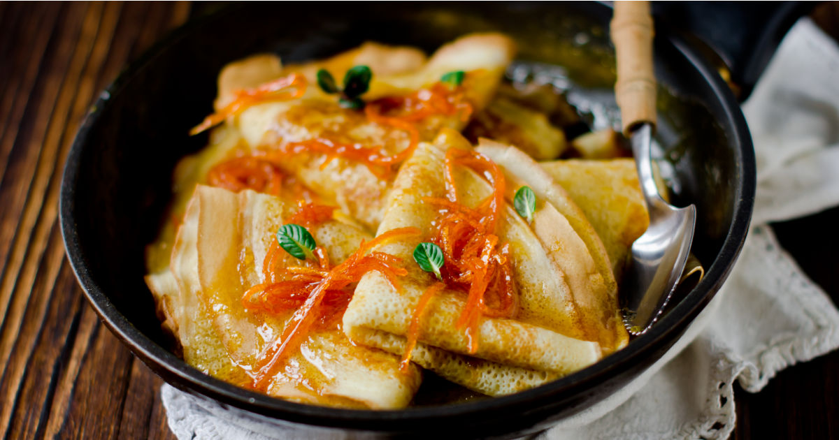 Dish of the French dessert of Crepes Suzette - thin, tender pancakes in a buttery, orange sauce.