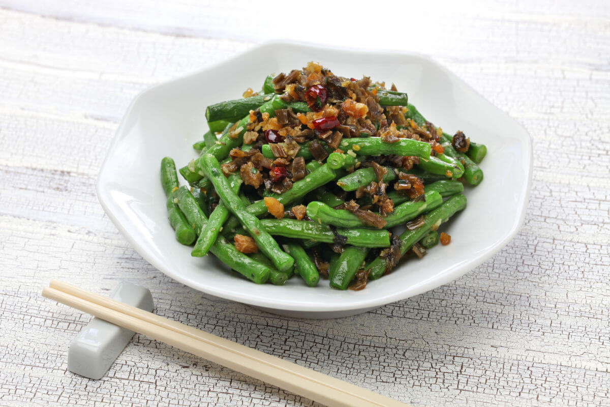 Plate of Sichuan Dry Fried Green Beans - dry fried with scallion garlic, ginger, red chiles, soy sauce, pickled greens, and sesame oil