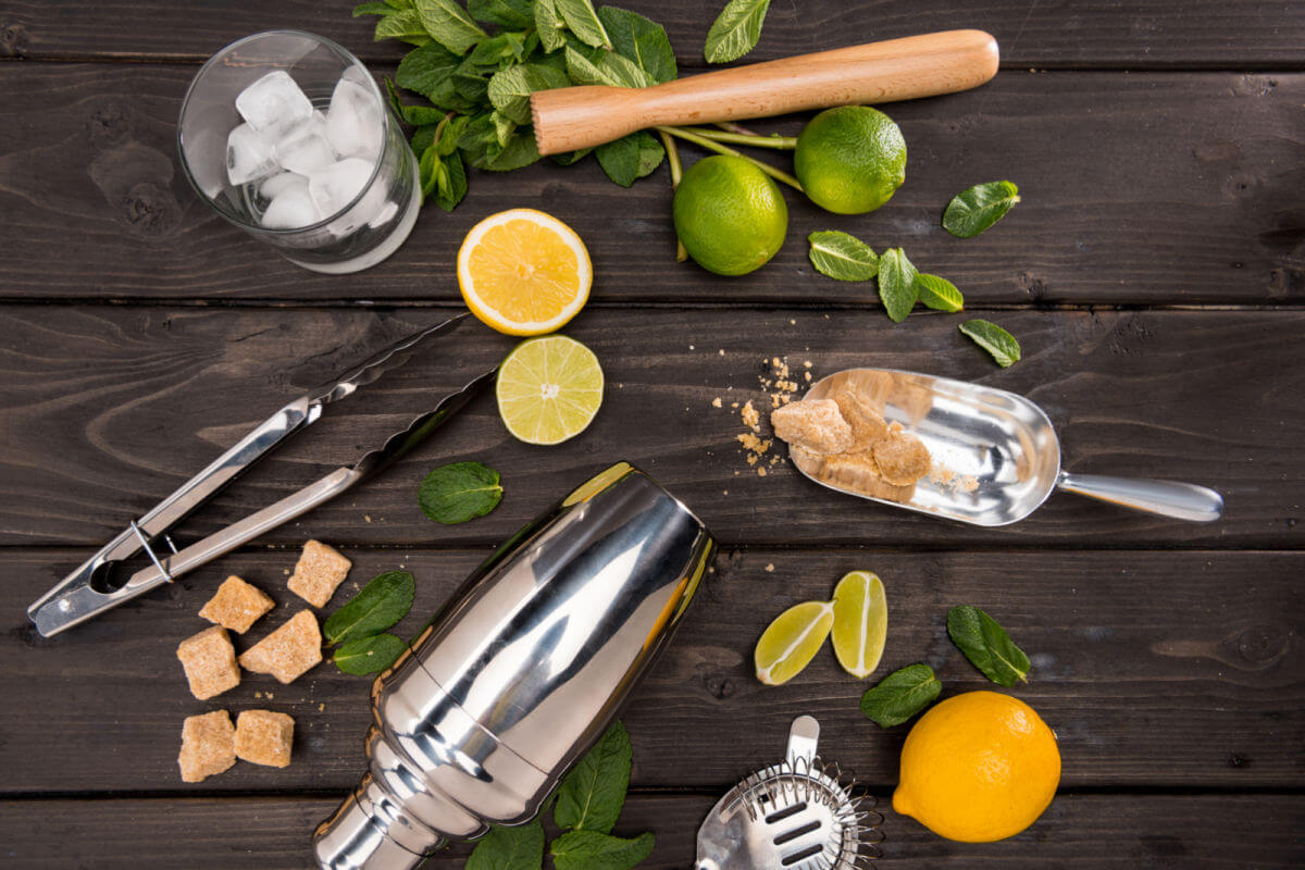 Ingredients for a classic mojito cocktail on a driftwood board