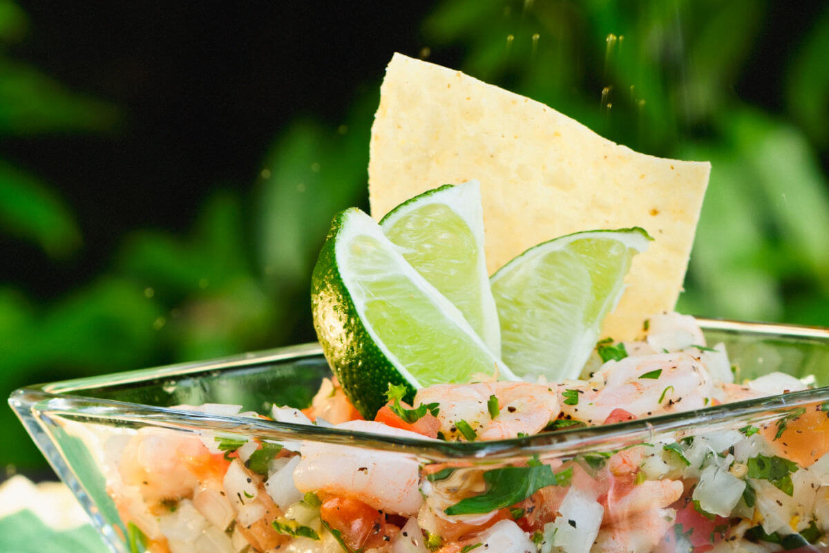 Glass bowl of colorful Mexican Shrimp Ceviche garnished with lime wedges and tortilla chips.