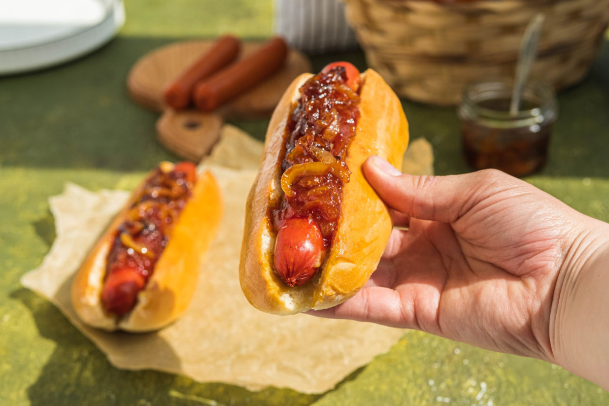 Hand holing a NYC-style dirty water dog with onion sauce