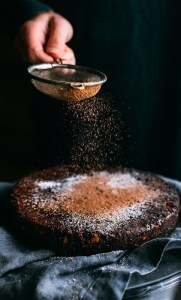 a person powdering a cake
