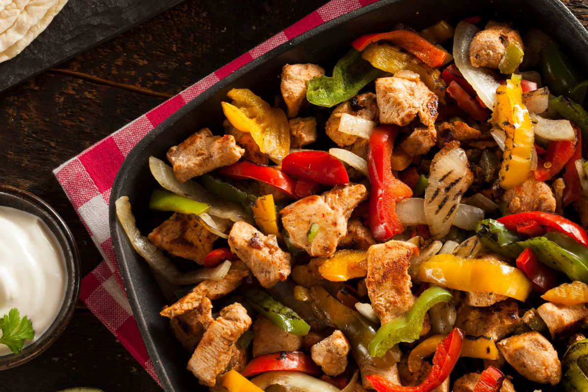 Cast iron pan with flavorful chicken fajitas - marinated chicken strips, onions, and green, red, and yellow bell peppers. Sides of guacamole, shredded cheese and a fresh lime are on the side.