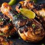 Slate plate of spicy grilled jerk chicken drumsticks garnished with chopped parsley and fresh lime.