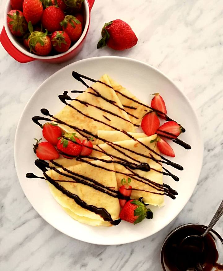 3 crepes folded into triangles on plate with strawberries and chocolate sauce