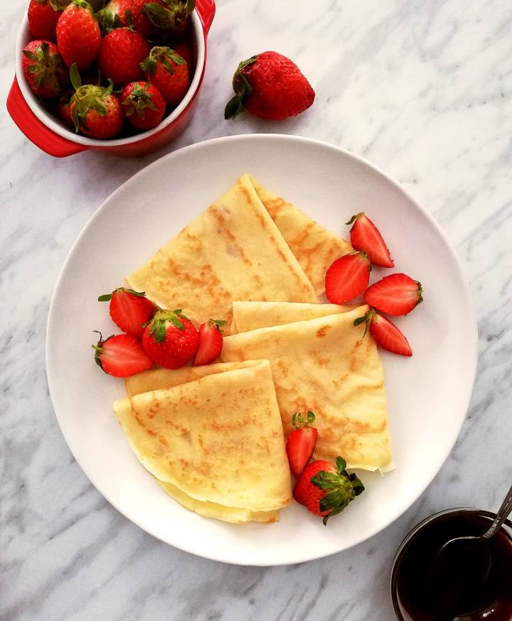3 crepes folded into triangles on plate with strawberries
