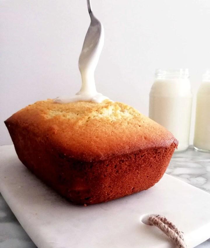 sour cream pound cake pouring glaze on top of cake