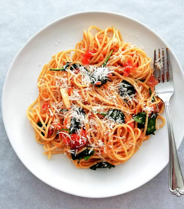 spinach pasta in plate with fork