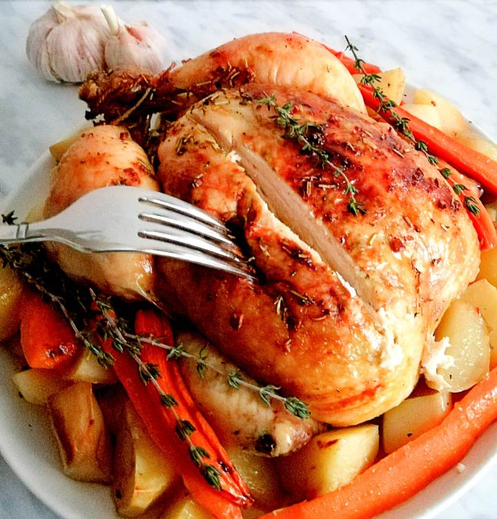herb roasted chicken with potatoes and carrots carved